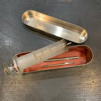 Big old glass syringe in it's metal box