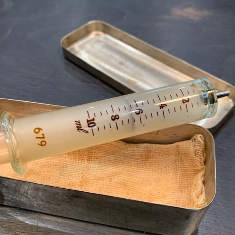 Old glass syringe in its metal case
