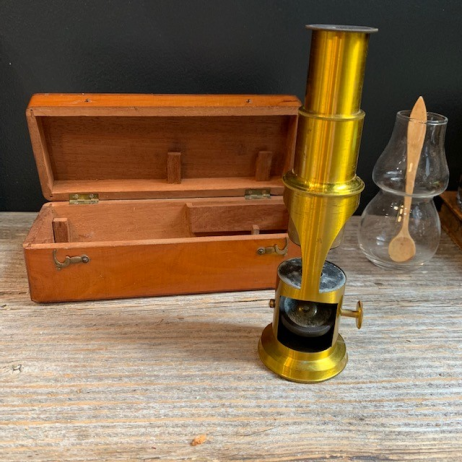 Old microscope in brass in it's mahogany wooden box